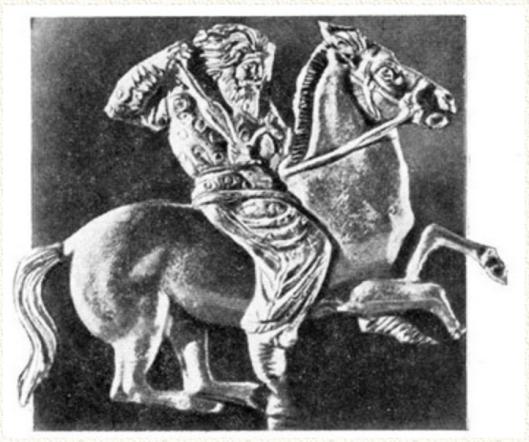 «Каноническое» изображение скифского всадника с копьём. Мужчина средних лет одет в типичную одежду казака -- «рубаху в горошек» и просторные шаровары с лампасами.